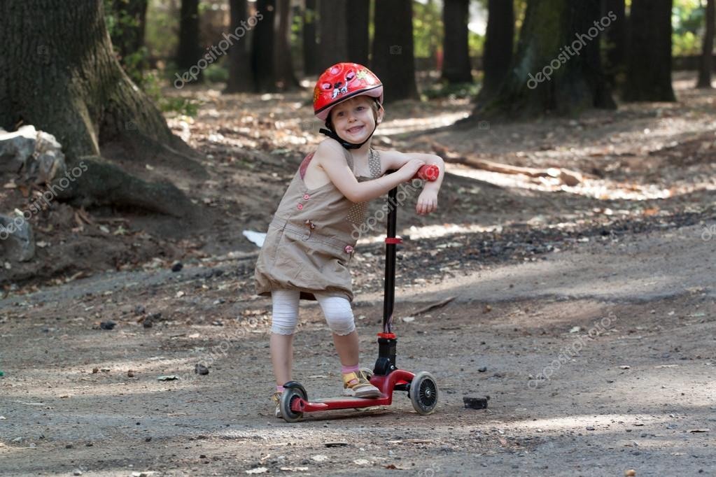 Portrait of cute little girl with scooter in city park — Stock Photo #13904774