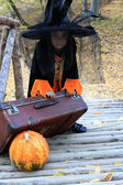 Witch child with a pumpkin on Halloween — Stock Photo