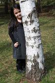Schattig klein meisje verstopt achter berk — Stockfoto