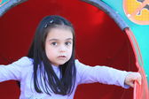 Cute little girl playing on a slide — Stock Photo