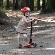 Happy little girl playing with scooter in park — Stock Photo #29451443