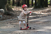 Happy little girl playing with scooter in park — Stock Photo