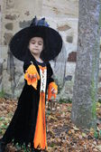 Witch child with latern and pumpkin — Stock Photo