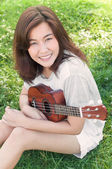 Asian young woman hug her ukulele in the park — Stock Photo