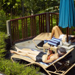 Women sunbathing beside pool — Stok fotoğraf