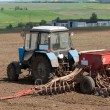 Stock Photo: Tractors planting farm fields