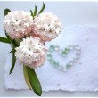 Three White pink hyacinth flowers with a heart from pearl beads on white handmade paper — Stock Photo