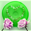 Two pink roses with a heart from glass beads on green glass plate — Stock Photo #24449199