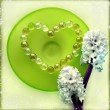 Hyacinth flowers with a heart from pearl beads on green glass plate — Stock Photo