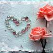 Grunge two Beautiful pink Roses Background with a heart from glass beads - Stock Photo