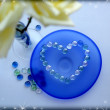Two white roses with a heart from glass beads on blue glass plate — Стоковая фотография