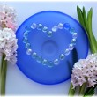 Hyacinth flowers with a heart from pearl beads on blue glass plate — Stock Photo #24449469