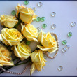 Yellow Roses flowers with a pearl bead thread on light blue background with glass balls — Стоковая фотография