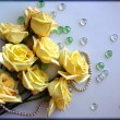 Yellow Roses flowers with a pearl bead thread on light blue background with glass balls — 图库照片