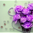 Pink Roses flowers with a pearl bead thread on light blue background with glass balls — Foto de Stock