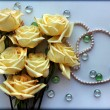 Yellow Roses flowers with a pearl bead thread on light blue background with glass balls — Stock Photo