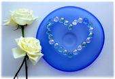 два белых роз с сердцем из стеклянных бусин на синей стеклянной пластины — Стоковое фото