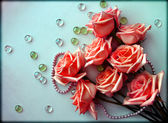 Pink Roses flowers with a pearl bead thread on light blue background with glass balls — Stock Photo