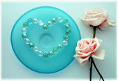 Two pink roses with a heart from glass beads on blue glass plate — Stock Photo
