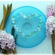 Hyacinth flowers with a heart from pearl beads on blue glass plate — Stock Photo
