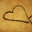 Drawing heart with a stick on wet sand at the beach, making heart shape — Stock Photo