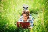 Girl reading a book lying in the tall grass — ストック写真