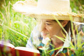 Girl reading a book lying in the tall grass — Foto de Stock