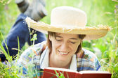 Girl reading a book lying in the tall grass — Stok fotoğraf