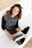 Woman with laptop on white sheet in her bed at home — Stock Photo