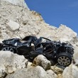 Car wreck below cliffs - Stock Photo