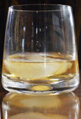 A Glass of Whisky reflected on the Table — Stock Photo