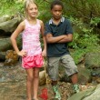 Boy and girl in the stream. — Stock Photo