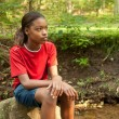 Stock Photo: AfricAmericgirl sitting on rock