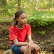 African American girl sitting on a rock — Stock Photo
