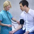 Female doctor checking young man blood pressure — Stock Photo