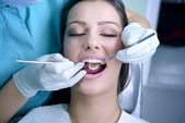 Beautiful young woman visiting dentist for dental checkup — Stock Photo