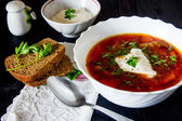Big bowl of borscht with sour cream and herbs — Stock Photo