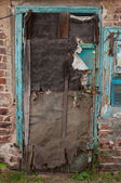 Old dilapidated ragged door — Stock Photo