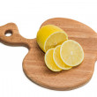 Kitchen chopping board with lemon slices — Stock Photo #38937341