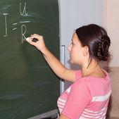 Girl writes on the blackboard, Ohm — Stok fotoğraf