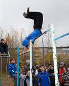 强青少年运动员在单杠上做运动 — 图库照片