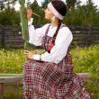 Girl in national costume paints a spinning wheel — Stock Photo #13837150