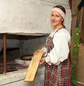 Dívka v kroji připravuje jídlo na sporáku — Stock fotografie