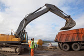 Excavator bucket on a dump truck lifted — Stock Photo