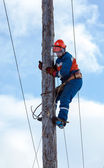 Electrician climbs a power pole — Stock Photo