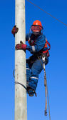 Electrician climbs the pole transmission line — Stock Photo