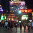Stock Photo: PATONG, THAILAND - APRIL 26, 2012: People walk in evening on