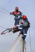Two electrics working on top of an electricity pylon — Stock Photo