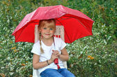 Little girl under a red umbrella — Stock Photo