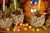 Caramel apple with fun pumpkin — Stock Photo